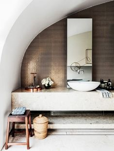 The curved ceiling of this Sydney bathroom makes the room, but the copper penny round tile backsplash is the showstopper. The bathroom is accessorized with more copper accents, as well as raw...