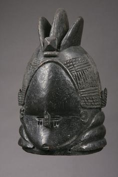 A Mende helmet mask Sierra Leone, of typical form, the mask with three large raised crests and finely incised coif encircling the upper portion, simple facial planes, the lower portion accented by stylized rolls of fat, pierced about the perimeter for attachment of fiber collar, black variegated surface. height 15 1/4in FOOTNOTES Masks of this type, commonly referred to as bundu were used by the Sowei society during girls initiations and are among the only masks in Africa to be danced by…