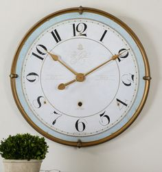 Torriana Wall clock: 32D Antiqued, gold metal frame with an antiqued ivory face and pale blue accent around inner edge.