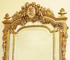 A Very Fine and Palatial French 19th Century Louis XV Style Gildwood Carved and Gesso Figural Mirror Frame. The upper cresting carved with a pair of Putti holding foliate and flanking a ribbon-tied center medallion with a portrait of a Royal Maiden. The foliate-carved sides with classically-draped figures of maidens terminating in scrolled corners, the lower panel section centered with a cherub mask. Circa: Paris, 1880