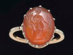 A ROMAN CARNELIAN RING STONE. CIRCA 2ND CENTURY A.D. The convex oval stone engraved with Fortuna, the draped goddess standing on a short groundline, supporting a cornucopia in her right arm, a branch and a ship's rudder in her left; mounted as a ring in a modern gold setting