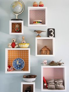 """Out of the Box: On another wall in the bedroom, wooden cubbies are hung for displaying knickknack items. Colorful fabric swatches used as backing make bright accents against the wall. The boxes can be easily rearranged and added to over time."""