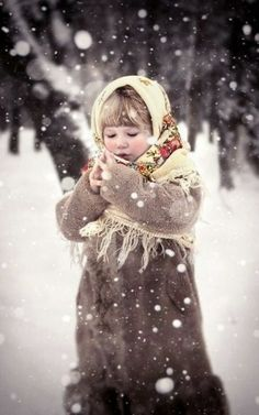 Russian girl in a warm coat and a traditional shawl is standing in the winter park during the snowfall.