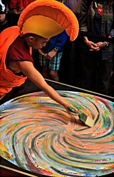 The Buddhist monks create sand works like this one as a form of meditation, drizzling the sand out from small metal funnels. The image incorporates icons that include geometric shapes and ancient spiritual symbols. A ceremony celebrated the completion of the sacred mandala, and ended with a monk wiping the sand away – a symbol of the impermanence of things.