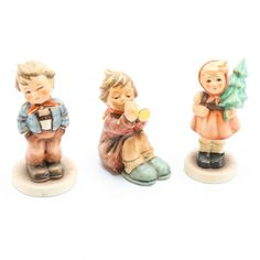 "A selection of three Goebel Hummel figurines. Featured figurines from left to right are titled Scamp, Girl With Trumpet, and Girl With Fir. The underside ""Goebel, Germany"" and maker's marks indicate production in the 1990s."