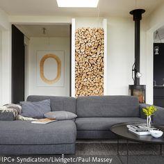 Ein skandinavisches Flair vermittelt dieses gemütliche Wohnzimmer mit Kamin. Das Kaminholz wird durch das Wandregal zur Deko umfunktioniert und die ruhigen,  …