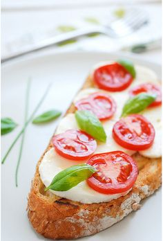 Rye bread with feta pieces, sliced grape tomatoes and mint