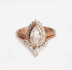 Halo Pear Diamond Ring with nesting diamond crown band. Instead of marquise diamond at the bottom we can also set pear diamond. This set is available in 14k/18k rose, white and yellow gold, palladium or platinum. Main stones can be: sapphire, diamond, moissanite, morganite, opal, moonstone,
