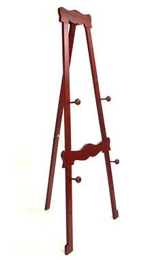 Georgian Display Easel.  Simple and elegant, this easel is crafted in the Georgian furniture style. It has a dark cherry finish and pre-drilled peg holes at regular intervals. The pegs are easy to adjust. Any environment will respond willingly to this tasteful piece. The easel ships collapsed with minimal assembly requirements.
