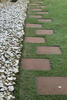 Caminho em placas cerâmicas intercaladas e entremeadas por grama; ladeadas por faixa em seixos brancos.