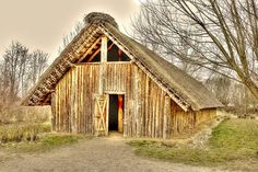 """Viking longhouse reconstruction in northern Germany. The """"smoke hole"""" in the roof remained a feature of nothern german, and danish-jutish farmhouses, until the 1930ies... So does the wagon wheel on the roof, which allowes storks to build their nests on it."""