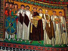 547 AD - Ravenna - San Vitale- Imperial Portrait of Emperor Justinian 1 and his Retinue.jpg  This mosaic shows Justinian 1 holding a golden bowl as a gift to Christ, who shown seated in the Apse lunette mosaic.  Justinian is richly robed in royal purple, and attended by twelve men, (two are almost hidden behind the group of soldiers on the left).  The group includes the Archbiishop Maximian of Ravenna, who is shown holding a cross.  Maximian's importance is emphasized by the fact that o...