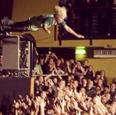 Matt Shultz from cage the elephant jumping onto a crowed of people