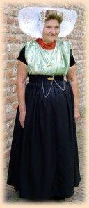 De kleding van de vrouw uit Arnemuiden vindt, net als die van Nieuw-en Sint Joosland, zijn oorsprong in de Zuid-Bevelandse dracht. De vrouw draagt een ondermuts van broderie. Over de ondermuts wordt een klein blauw tussenmutsje gedragen. De bovenmuts is gemaakt van broderie, slechts zelden van kant, en heeft de vorm van een dubbele schelp. Aan het oorijzer in de ondermuts zijn gouden krullen bevestigd. Verder draagt de vrouw in de ondermuts gouden mutsenspelden en draagt ze het haar in een…