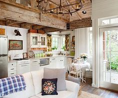 An open floor plan encourages interaction between family members in this quaint cottage. Vintage finds come together in the kitchen and living room to make the space overflow with character. Compact appliances and a corner sink maximize limited space./
