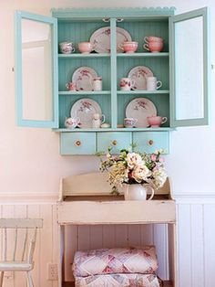 pink china in shabby blue cabinet