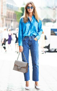 A blue button-down is worn with raw-hem jeans, suede pumps, and a Gucci bag