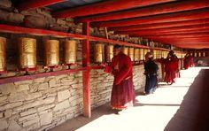 Tibetische Pilger beten und rollen die Gebetsmühlen im Jokhang Tempel. Entdecken Sie Tibet in kleiner Gruppe mit Besuche zahlreicher tibetischen Highlights.