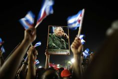 Pictures of the Year 2016:     Cuba ‐ Fidel Castro's Death:    People hold up an image of former Cuban leader Fidel Castro at a tribute to Castro in Santiago de Cuba, Cuba, December 3, 2016.