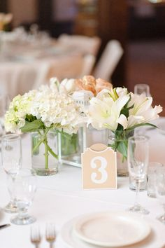 Classic wedding centerpiece + table number idea - floral centerpiece with winter white assortment of lilies, hydrangeas and tulips and simple table numbers {Fowler Studios}