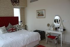MY HOME - Bedroom, red chesterfield velvet headboard on divan, brick effect wallpaper, mannequins, cushions, dressing table, red stool, cherub picture #Dubai #apartment