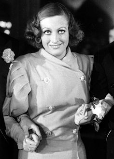 1932: Joan Crawford at the Grauman's Chinese Theatre premiere of her feature Rain, where she walked tightly arm-in-arm with Billy Haines, Robert Young, and husband Douglas Fairbanks, Jr.