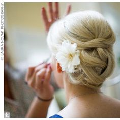 woven bun bridal updo hairstyle with flower