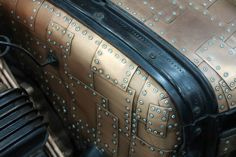 really amazing firewall and cowl on a hot rod that are covered with small riveted plates of what looks like brass. Pic 1