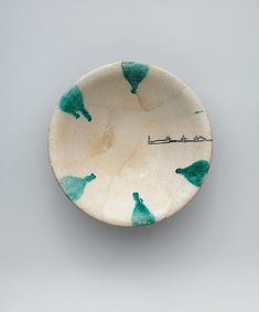 Imitation Green-Splashed Samarra Ware Object Name: Bowl Date: 9th–10th century Geography: Iran, Nishapur Culture: Islamic Medium: Earthenware; painted in black with splashes of green on opaque white (tin) glaze Dimensions: H. 2 1/2 in (6.3 cm) Diam. 8 1/16 in. (20.5 cm) Classification: Ceramics Credit Line: Rogers Fund, 1939 Accession Number: 39.40.10 Met
