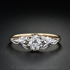 This two-tone (platinum over 18K yellow gold) .35 carat diamond engagement ring from the 1930s is as sweet as can be. The diamond is set in a classic 'buttercup' setting which adds extra diameter to the center which makes the diamond appear a little larger. The shoulders of the ring are adorned with a lovely floral sculpture in platinum. A beautiful little vintage treasure which we believe was originally produced in England.