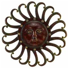 The face of this sun decor looks peacefully serene as rays of light curl around the accented edges of the orb.