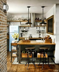 Small kitchen interior. Timber and steel bench, floorboards, exposed bricksl, pendant lights, subway tiles