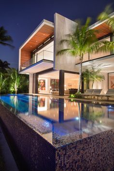 At the rear of this modern house, the interior spaces open up to the a swimming pool.