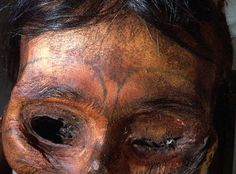 Detail of forehead tattooed Eskimo female mummy. The tattoo was created by soot-stained or dyed thread drawn under the skin by a needle.