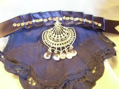 This is a navy blue hair comb featuring crocheted lace, navy blue satin ribbon with square sequins and glass beads and a silver dangle
