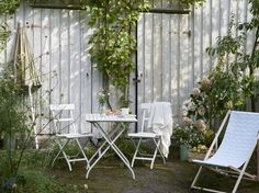a garden with a white small foldable table and two chairs all in painted solid balcony furnished small foldable