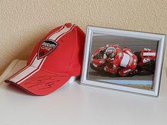 Loris Capirossi - Meervoudig Wereldkampioen - hand gesigneerde Ducati Cap ingelijste actiefoto  COA.  Loris Capirossi (Castel San Pietro Terme 4 april 1973) is een motorcoureur uit Italië die op 15 juni 2003 de eerste GP-overwinning op een Ducati behaalde in de MotoGP klasse. Capirossi heeft na Barcelona 2003 nog overwinningen geboekt in Motegi (Japan) en Sepang (Maleisië) in 2005. In 2006 won hij de seizoensopener in het Spaanse Jerez en op het circuit van Brno won hij ook. Dit…