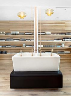 Cornices are commonly used to decorate the junctions between walls and ceilings, but at the Boston shop for skin and haircare brand Aesop, cornices cover the walls and form shelves for the brand's signature brown bottles.