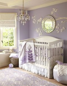 A classically styled white crib pops against lavender walls, sheeting and other accents to give this nursery its classic, feminine appeal. The dangling crystal chandelier and round mirror with a weathered finish add sparkle to the room. To make this nursery extra special, we created a three-dimensional wall mural with a mix of paper and paint to depict a graceful bird perched on a branch.