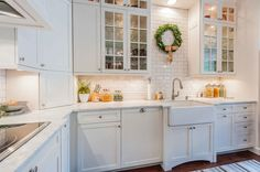 A boxwood wreath adds a merry touch to an all-white kitchen