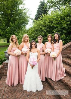 A beautiful image of the bride and her bridesmaids all in pink dresses.