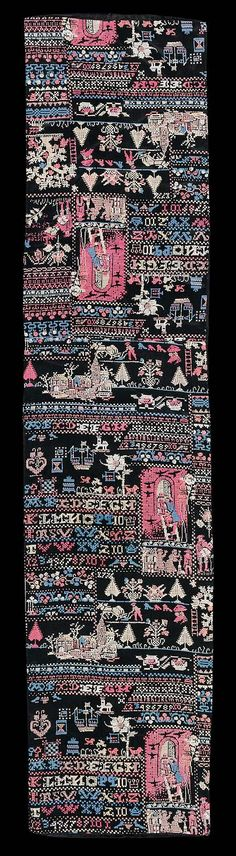 Black background with sampler motifs, alphabet, pastoral scenes, etc, in red, blue, white and tan. Lined with blacksilk.