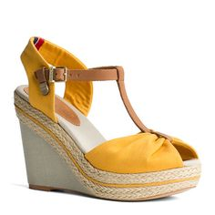 This summer's style highlight are espadrille wedge sandals. Canvas upper, peep-toe styling with gathered toe strap. Leather T-strap with branded, gold-toned buckle and rivet. Braided jute and canvas along the wedge. 11.3cm heel. Tommy Hilfiger ribbon at the heel, stamp on the leather patch on the cotton insock. Tunit sole.
