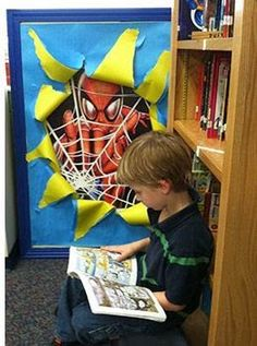 Spiderman peeking into the reading corner. LOVE this idea. Could get posters of the various superheros and do this for various centers around your room.