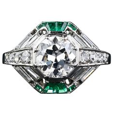 French Art Deco diamond ring from 1920s-30s 1.60 carat European-cut diamond in an octagonal setting accented with four tapered baguette-cut and four square-cut emeralds with eight whistle-cut diamonds.