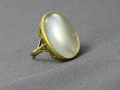 This moonstone, cut en cabachon is unusual in its scale, measuring a very large 1 inch long x 3/4 wide. The 18k gold work is very finely done with the stone hand set in a cut down claw mount. The ring has a large gallery that is all hand done with a series of S swirls, and a shank that is refined and simple. The condition is excellent with minor surface wear visible with a loop. It is beautiful, dramatic and completely original,English circa 1900.