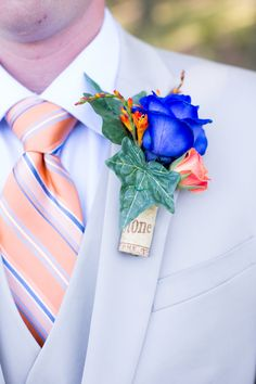 Groom Boutonniere orange, blue and a wine cork. This is so creative!