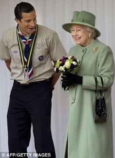 Britains Queen Elizabeth II speaks with Chief Scout, Bear Grylls during the review of Queens Scouts at Windsor Castle in Windsor in April 2012
