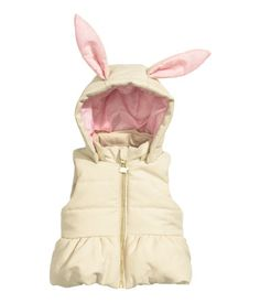 Padded vest with lined, detachable hood with padded ear appliqués. Zip at front and flounce at hem. Lined.