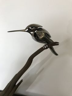 Hummingbird made from upcycled utensils and scrap metal perched on driftwood.